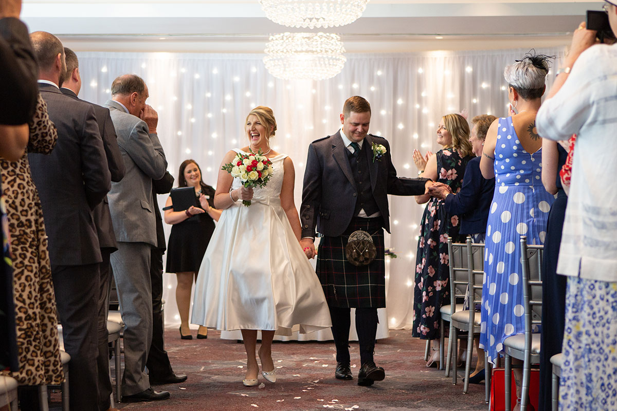 A couple walks down the aisle after saying 'I do'