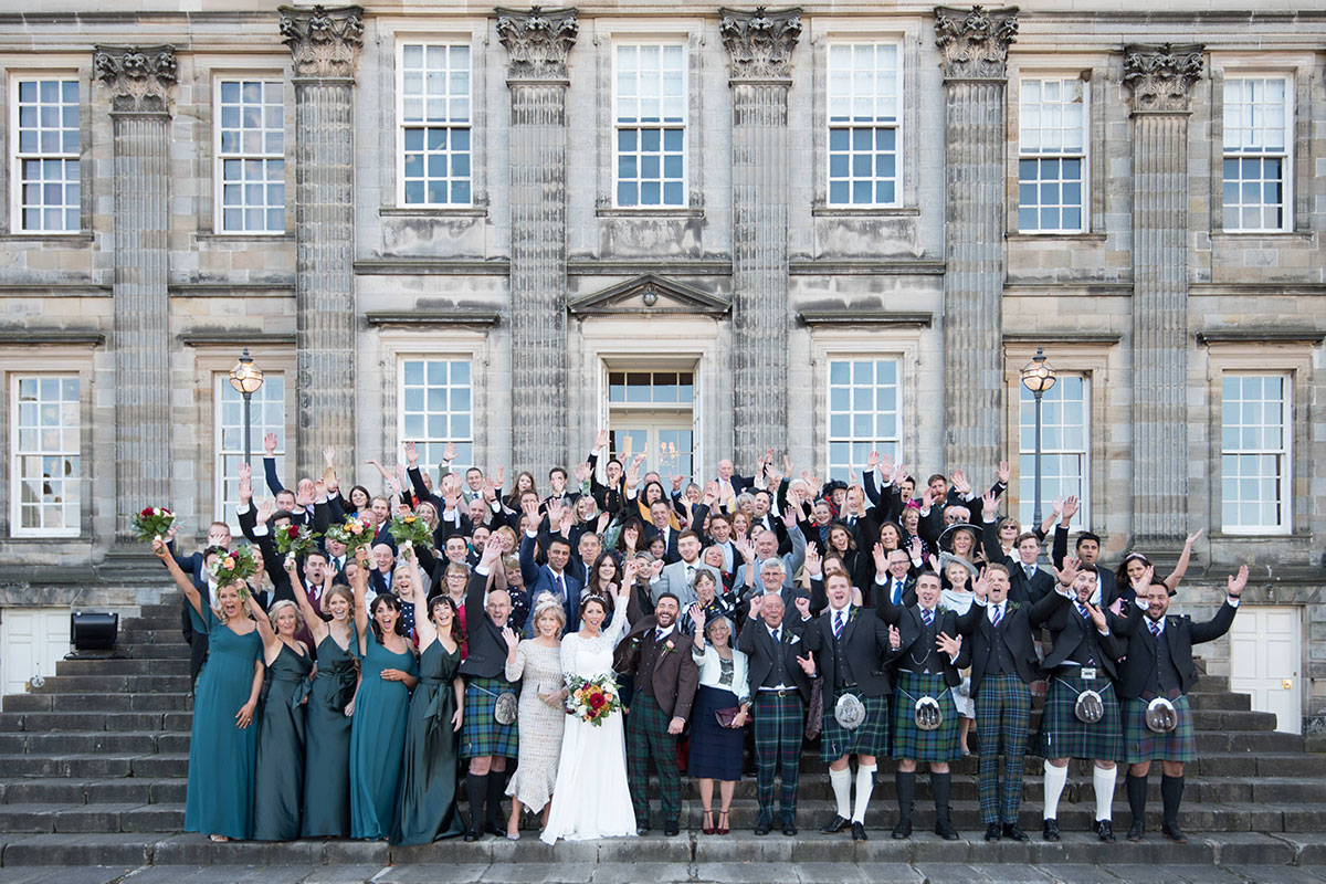 A group shot of all the guests standing on the steps leading up to the venue