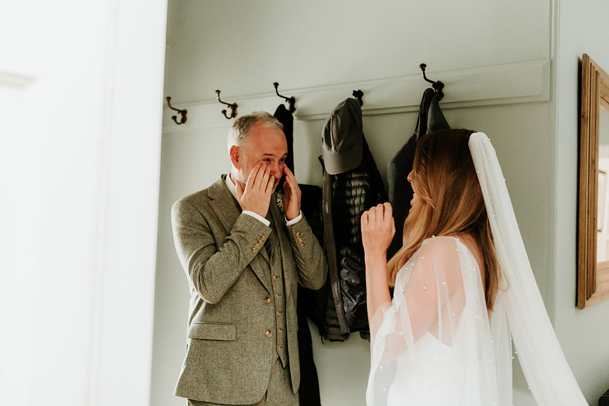 A father cries when seeing his daughter in her wedding dress for the first time