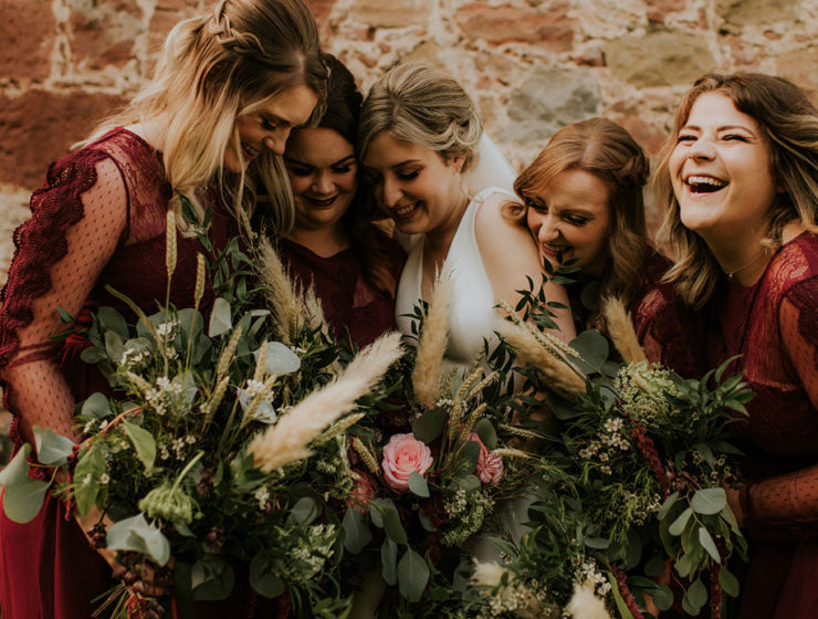 A bride and four bridesmaids hugging each other and laughing
