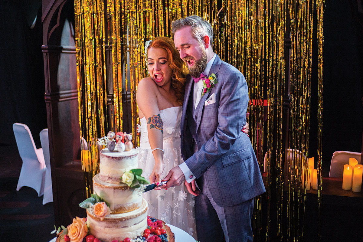 A couple cuts a white cake with flower decorations