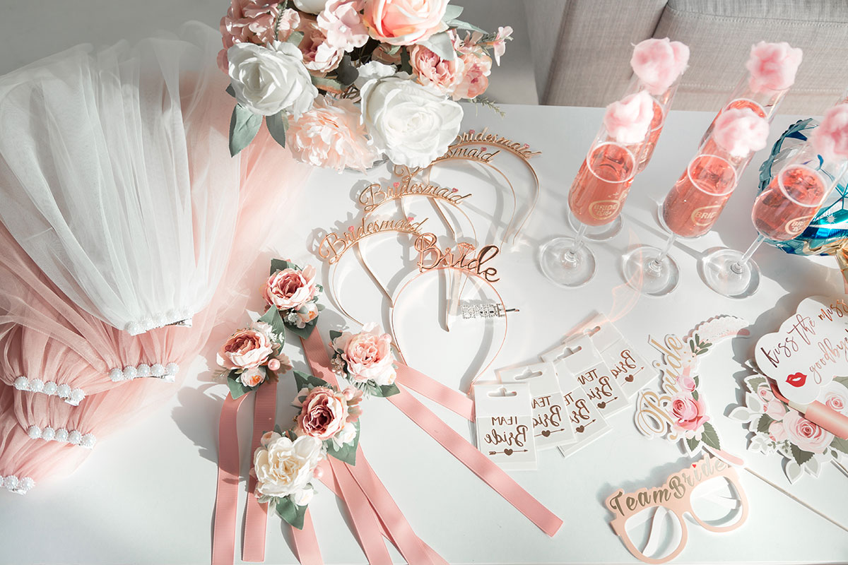 A table covered with hen party props, including veils, headbands, flowers, fake glasses and drinks