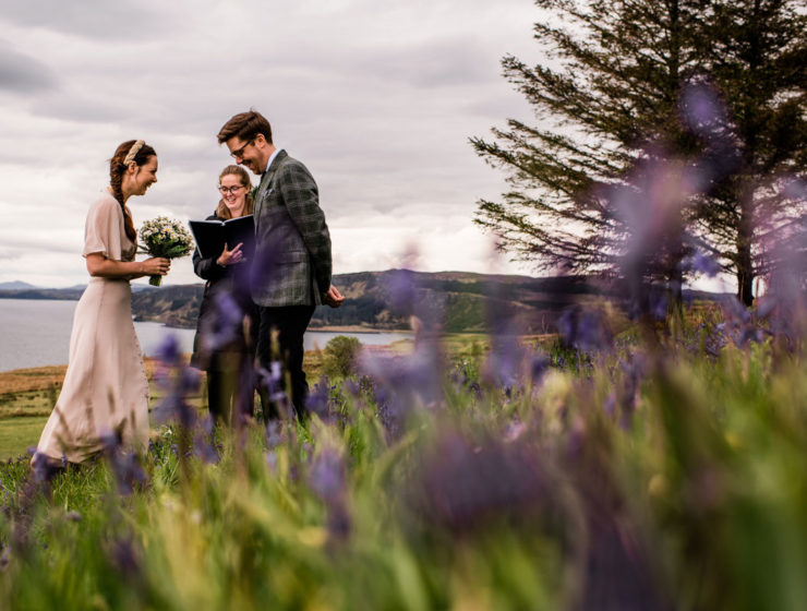 Bride and groom laughing while celebrant conducts wedding ceremony by a lake and tree in the countryside
