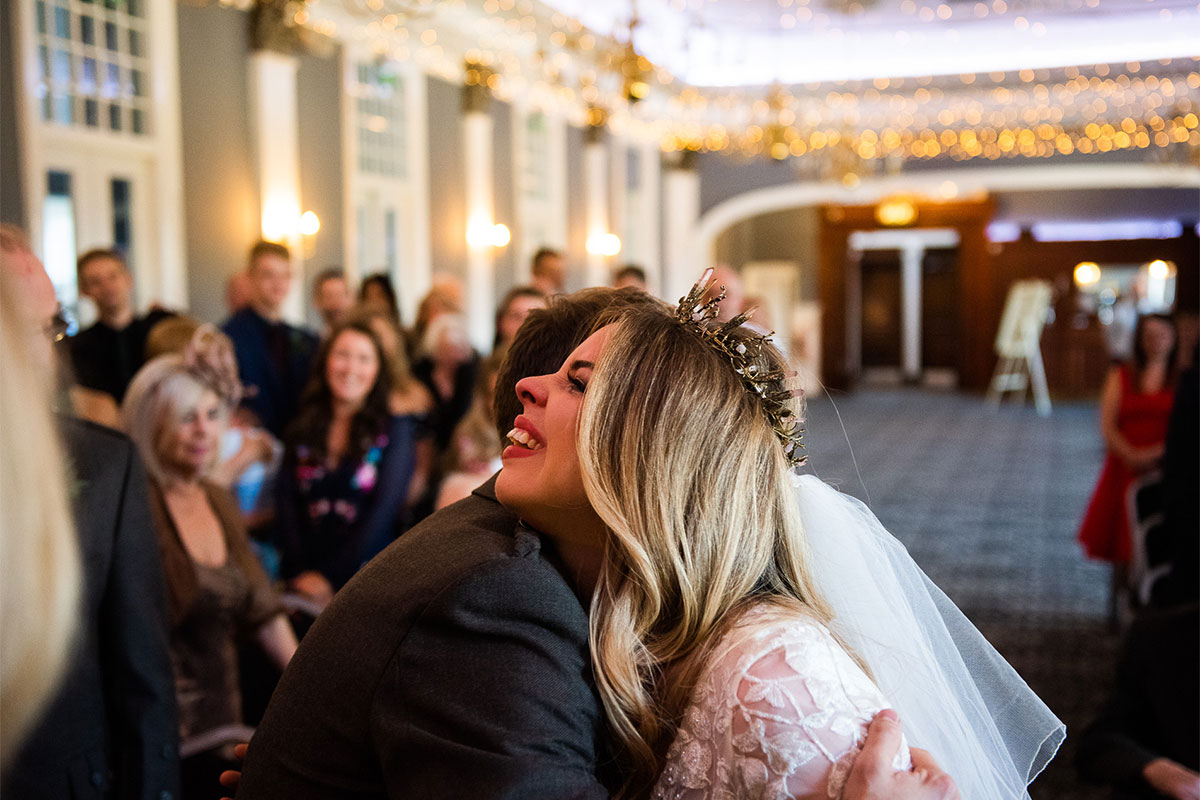 Bride and groom hugging during wedding ceremony with blurred out guests in background