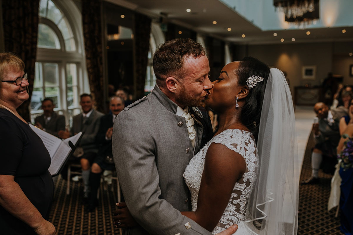 Bride and groom kissing at a wedding ceremony while happy guests and celebrant look on