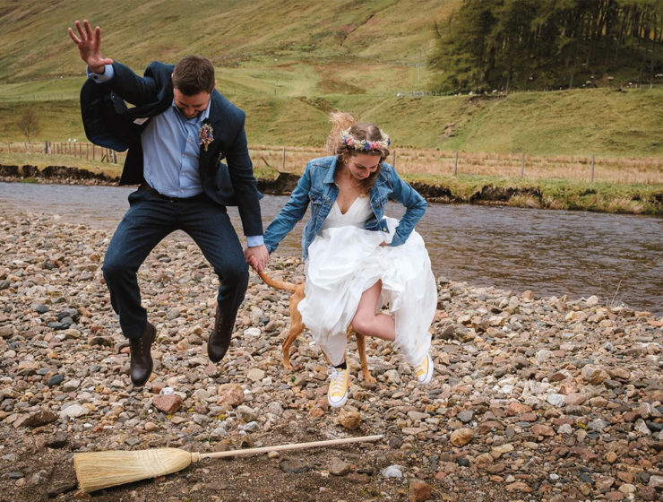 A bride and groom jump the broom