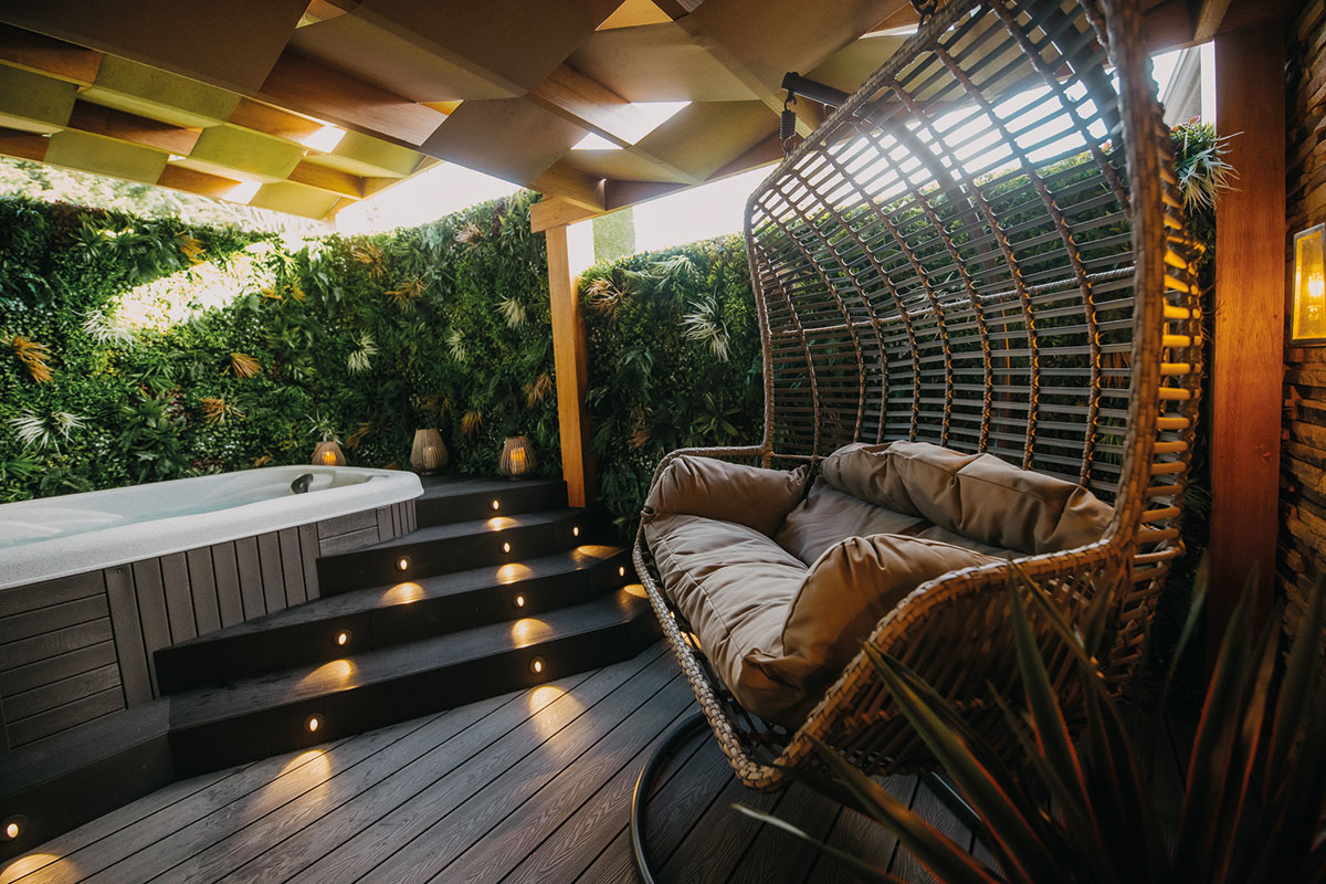 The outdoor space at The Busby Hotel, with comfortable seating and hot tub