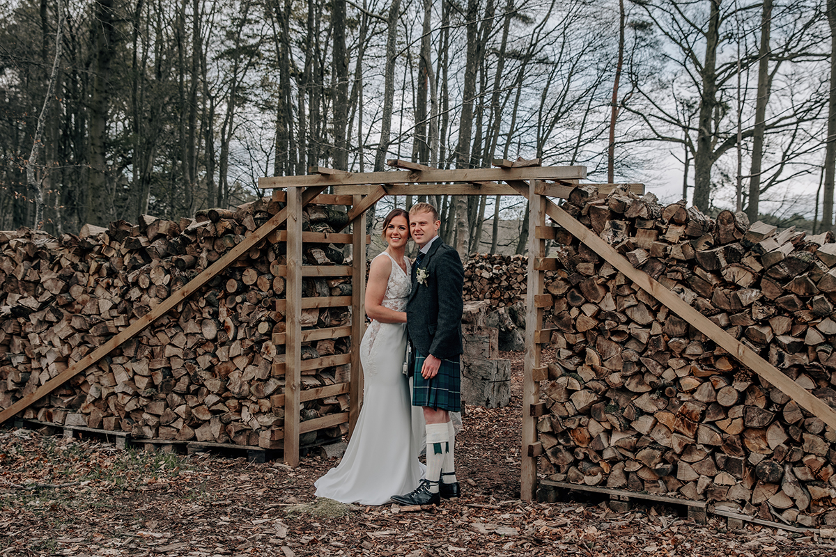 Couple pose by chopped wood in the grounds of Wedderlie House