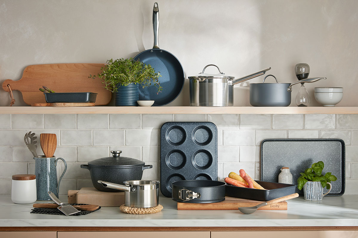 Various cookware pieces, including pots, pans and chopping boards, lined up on a kitchen work surface and on a shelf
