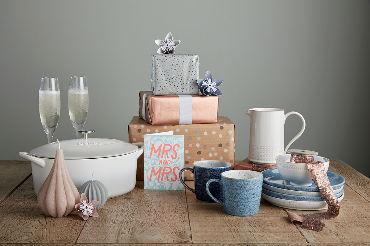 Presents on a table, some wrapped and some unwrapped, including champagne flutes, candles, mugs and a jug
