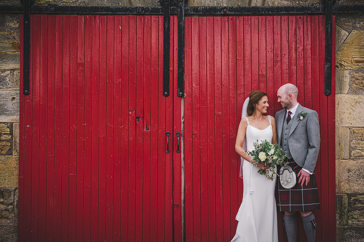 a bride and groom pose against a red painted door at Kinkell Byre