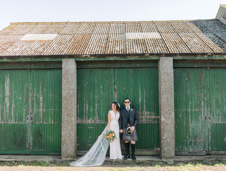 bride and groom standing against green painted door at Pratis Barns