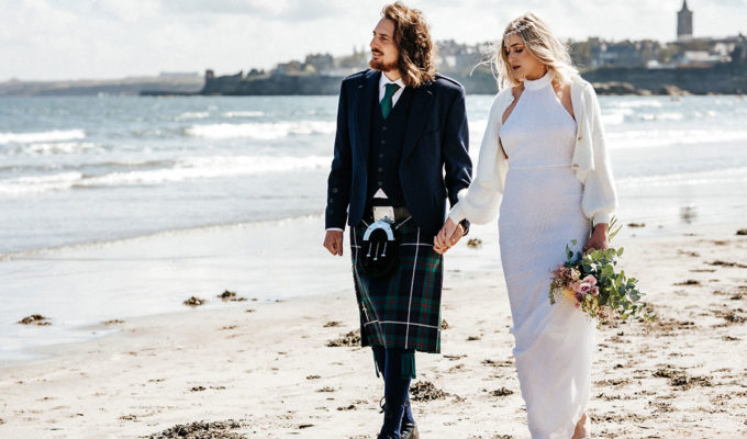 bride and groom walking along beach at St Andrews