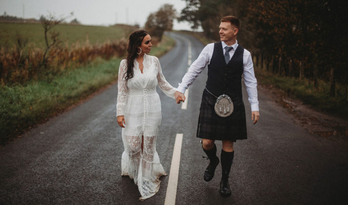 bride and groom walking hand in hand along road in Scotland
