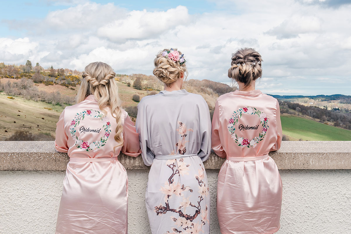 the back of a bride and two bridesmaids wearing floral dressing gowns looking out into countryside