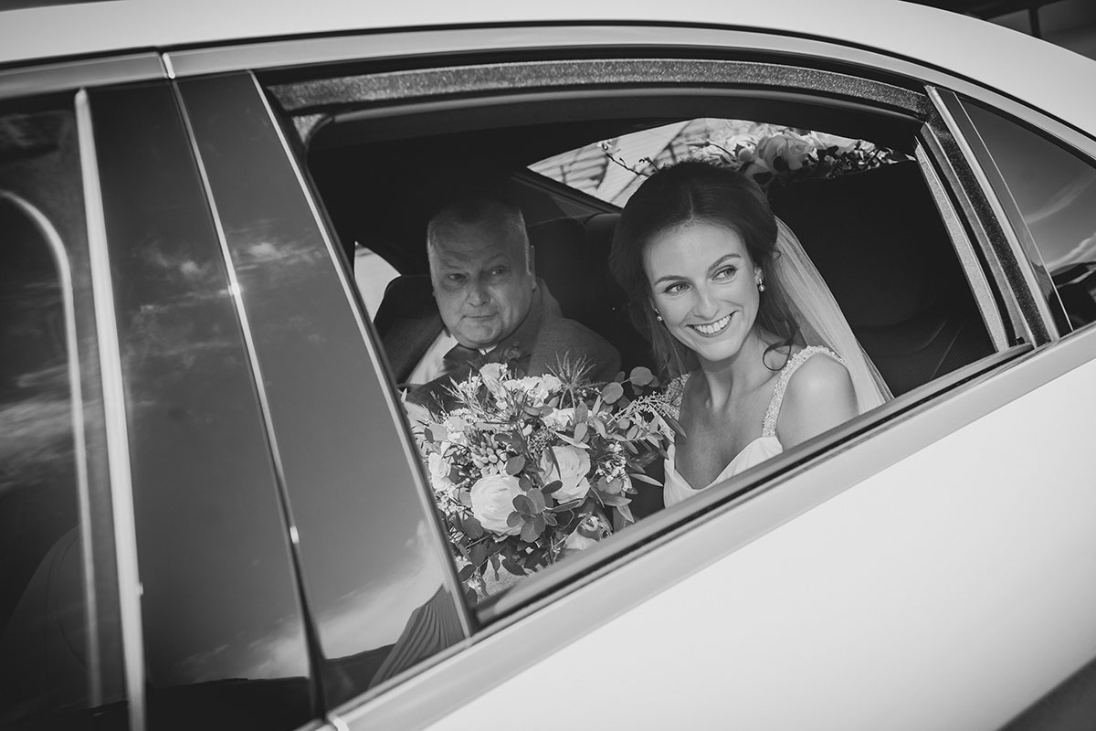 a black and white image of a bride looking out of a car window with man next to her