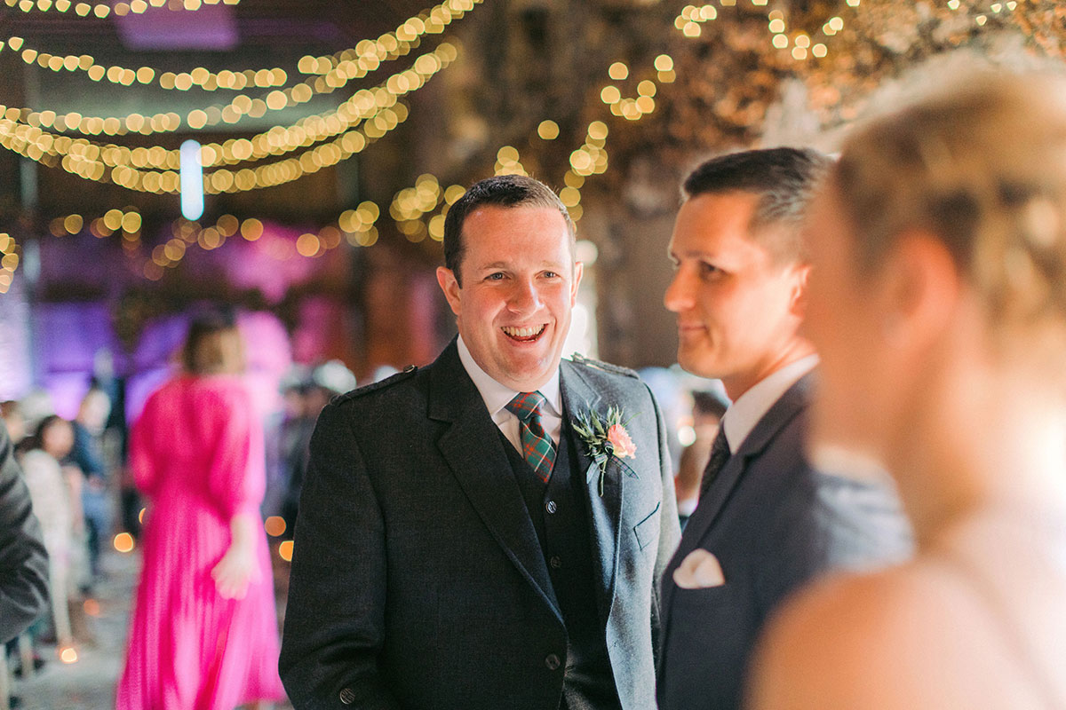 groom smiling with guests at wedding ceremony
