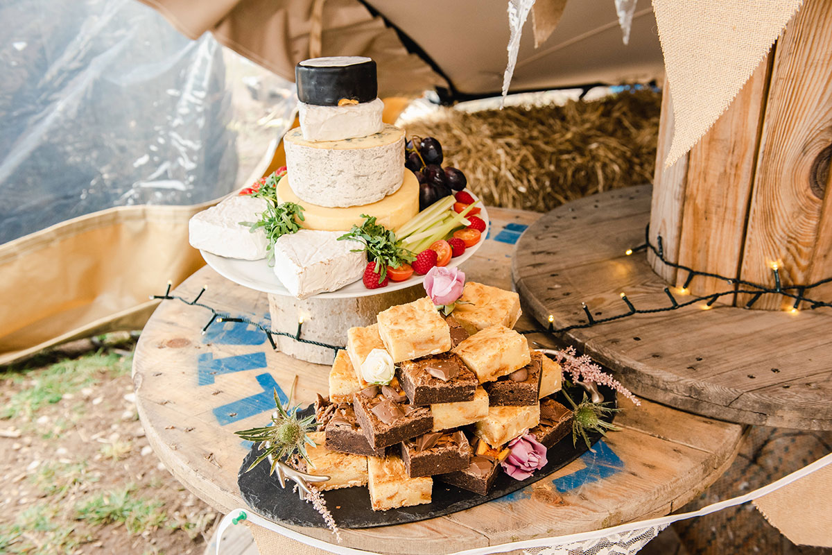 brownie and blondie stack and cheese tower on a rustic wooden presentation board at a wedding