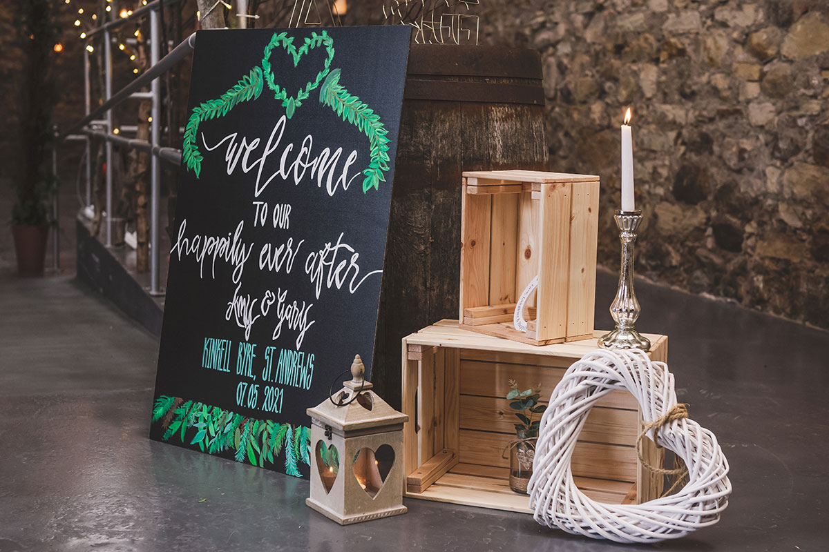 wedding chalkboard welcome sign with wooden crates and wicker white heart