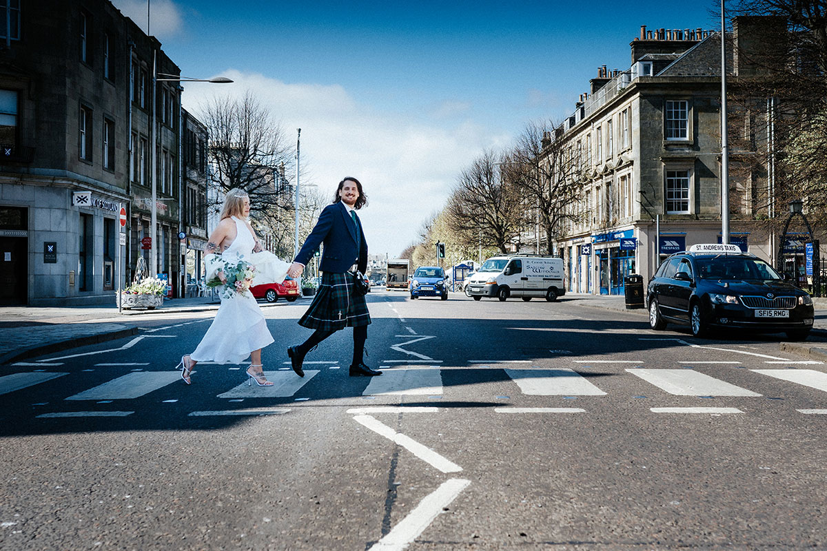 a bride and groom walking across a zebra crossing in St Andrews