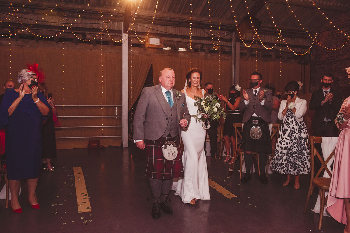 a bride on the arm of a man walking down the aisle during a wedding ceremony at Kinkell Byre while guests wearing masks look on