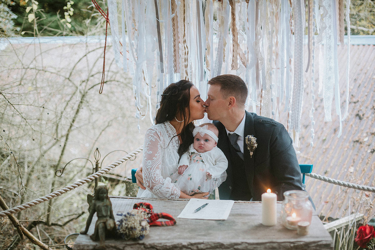 bride and groom kissing with baby on knee at signing table during wedding ceremony with macrame in background