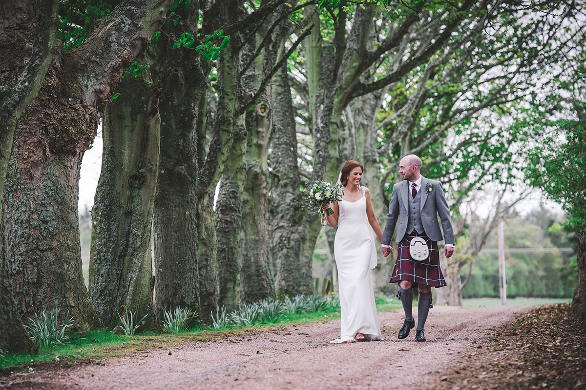 a bride and groom walk hand in hand along an avenue of trees