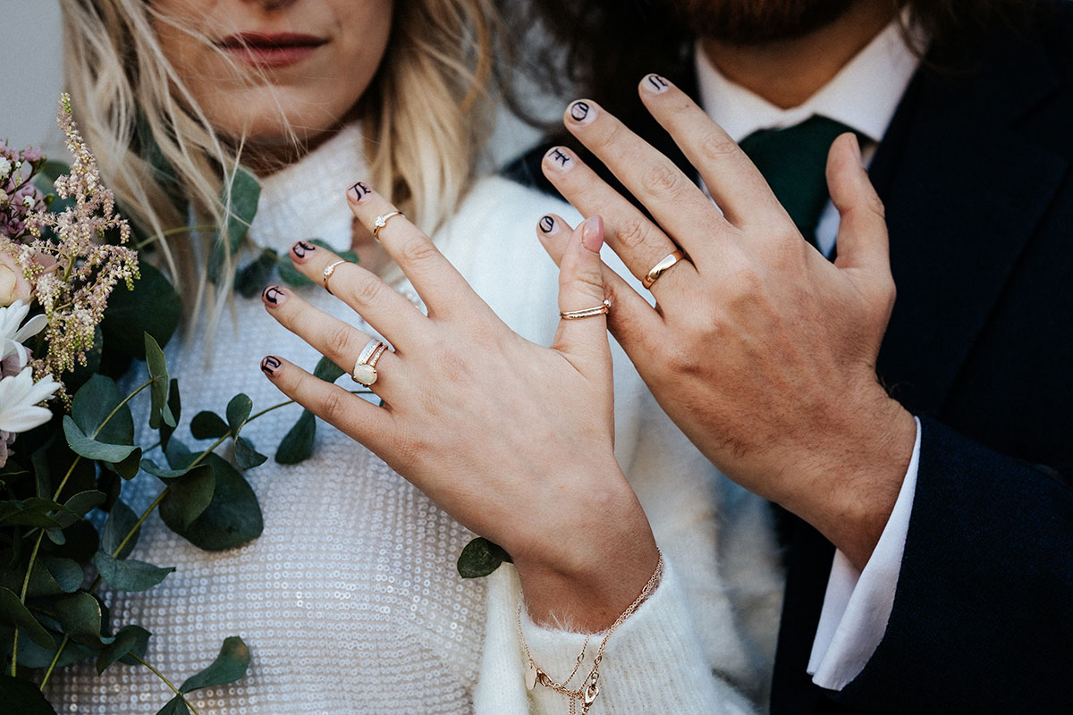 a bride and groom with painted nails and gold wedding rings