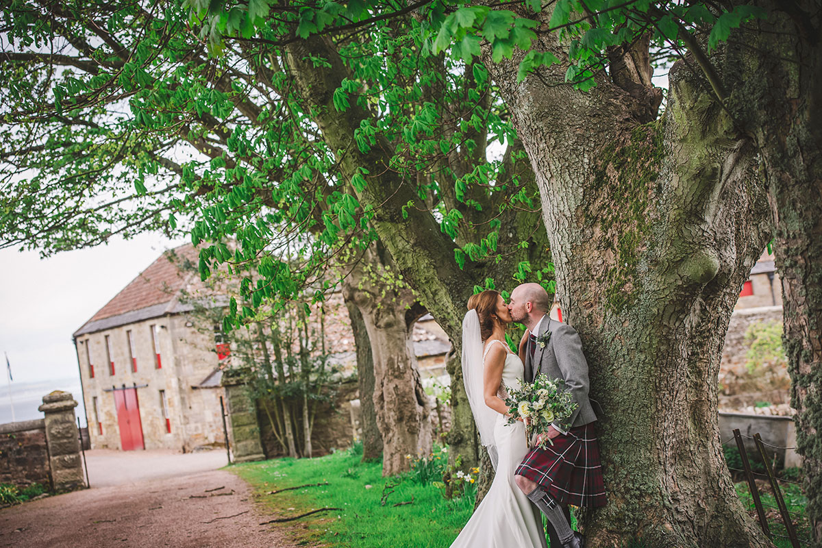 a bride and groom kiss by a tree with farm buildings in background