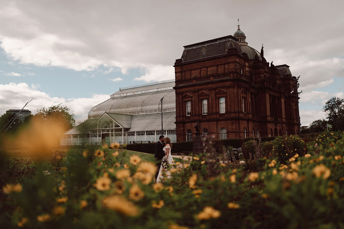 a bride and groom pose in front of the Winter Gardens in Glasgow Green