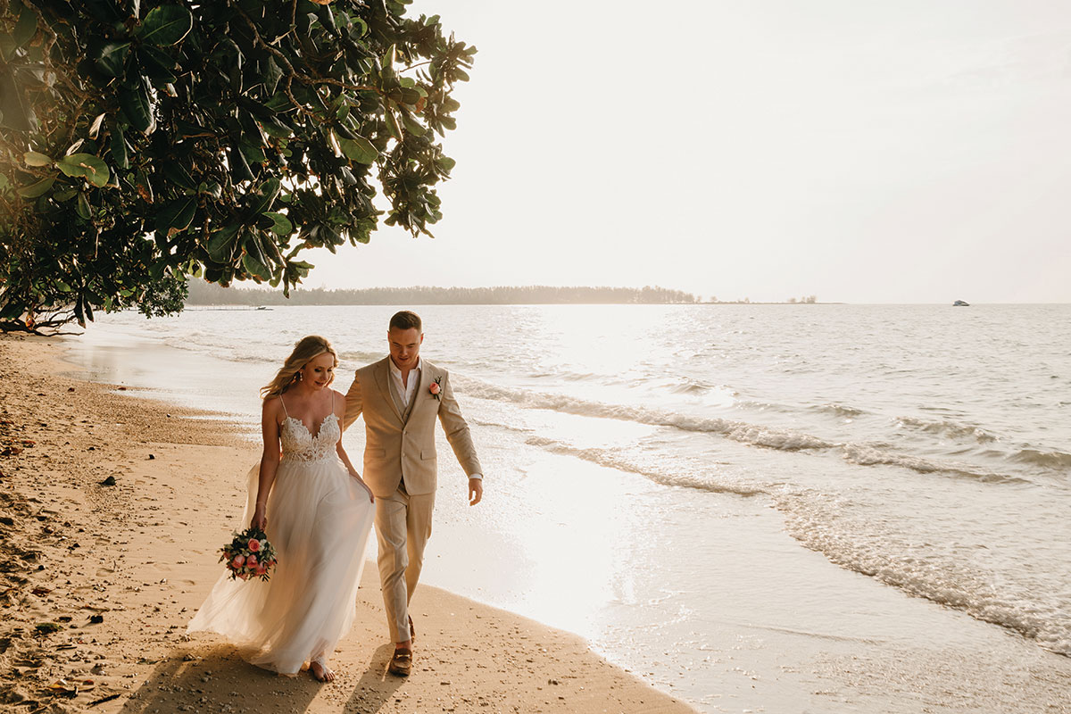 a bride and groom walking along the beach at The Sarojin in Khao Lak in Thailand