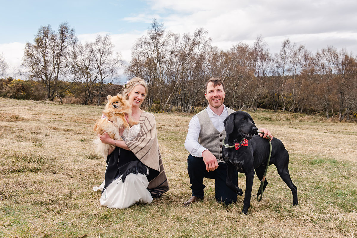 bride and groom kneeling in countryside with bride holding pomeranian dog and groom with black Labrador wearing red bow tie