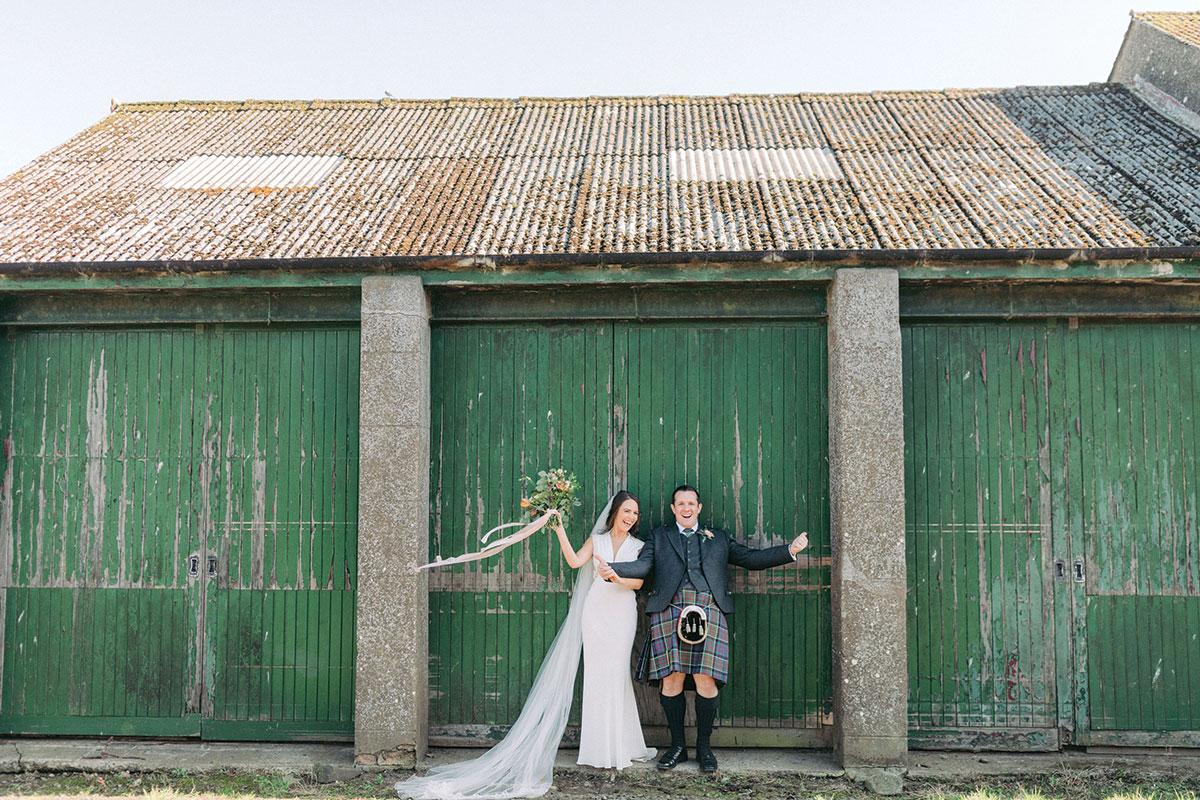 bride and groom posing against green painted door at Pratis Barns