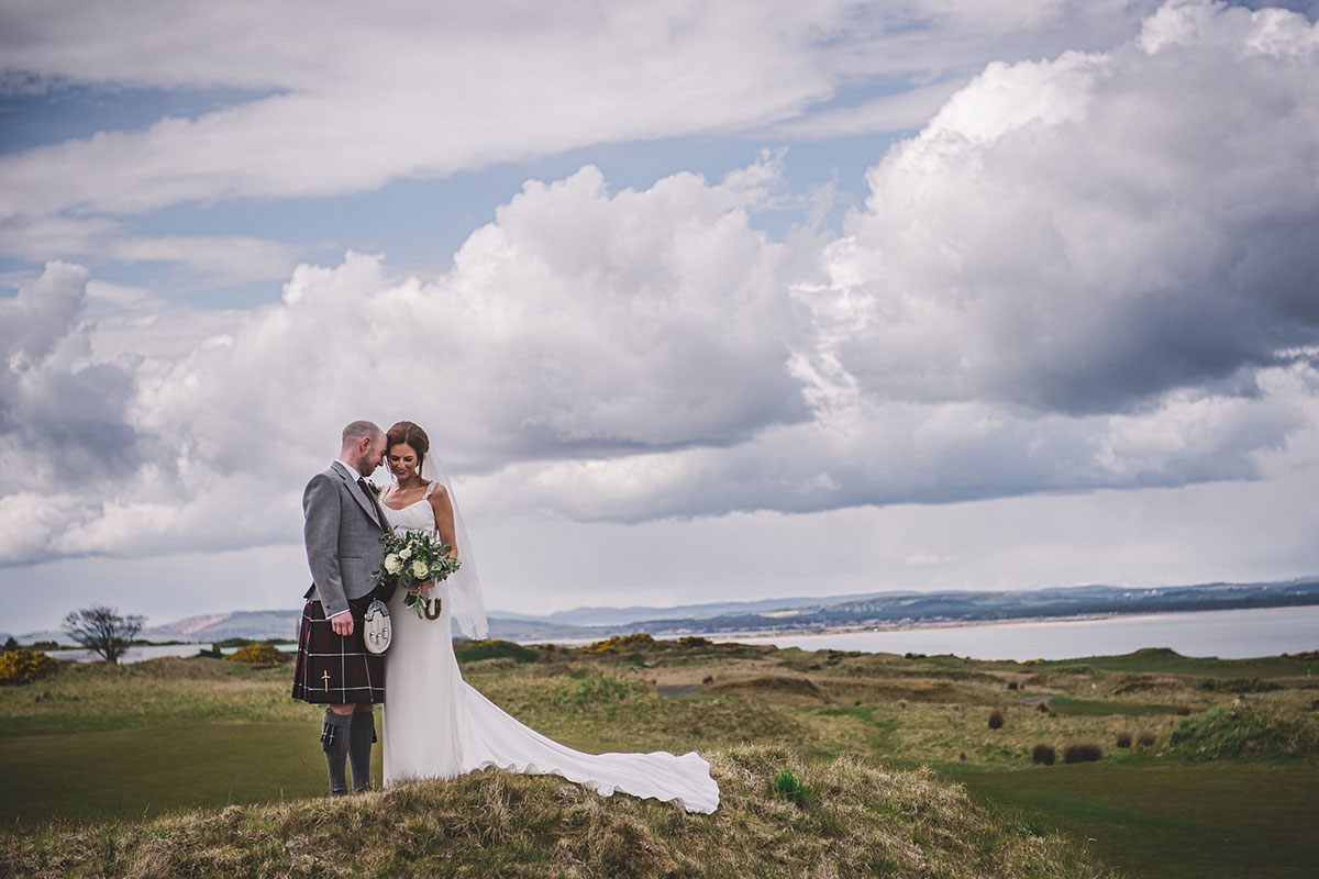 a bride and groom on a grassy hill with the North Sea and cloudy skies in background