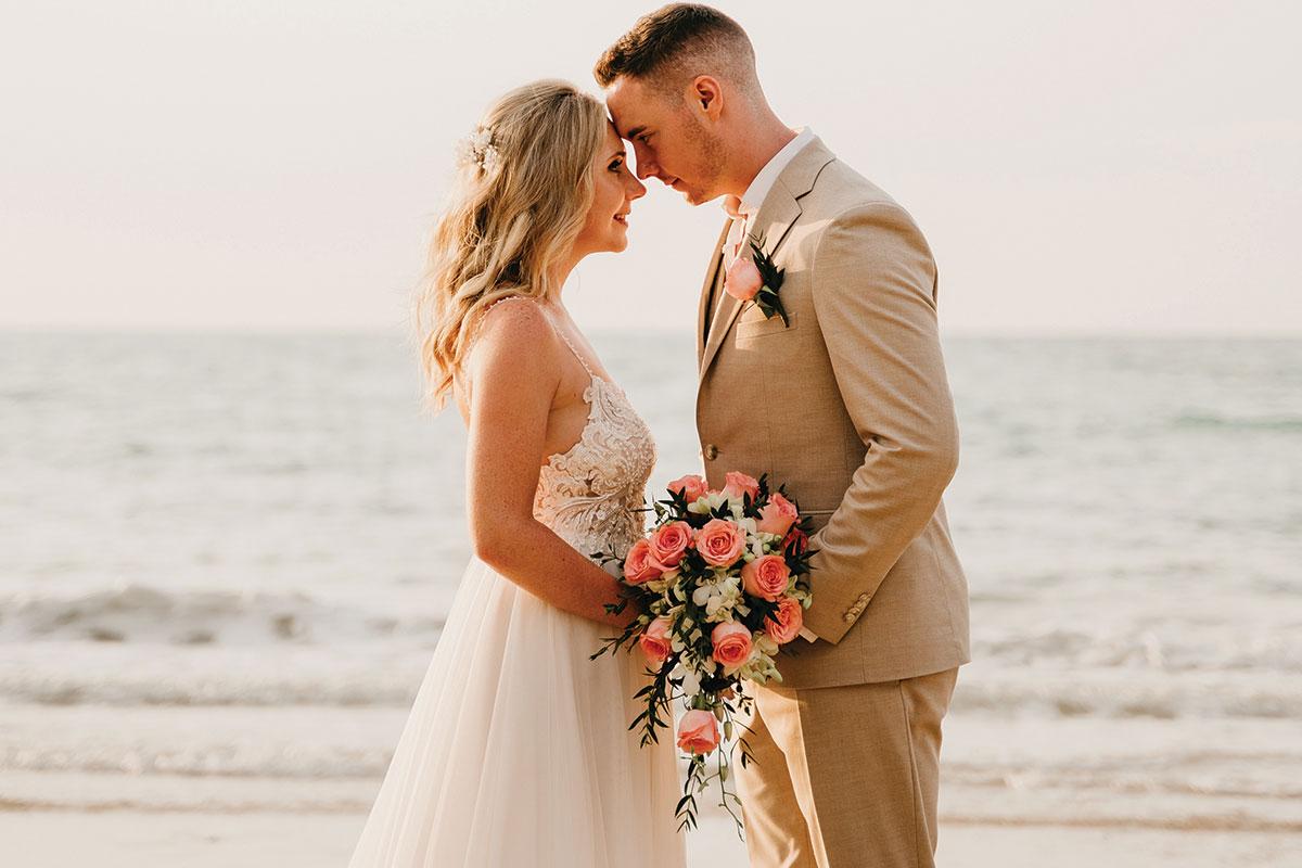 a bride and groom posing on a beach