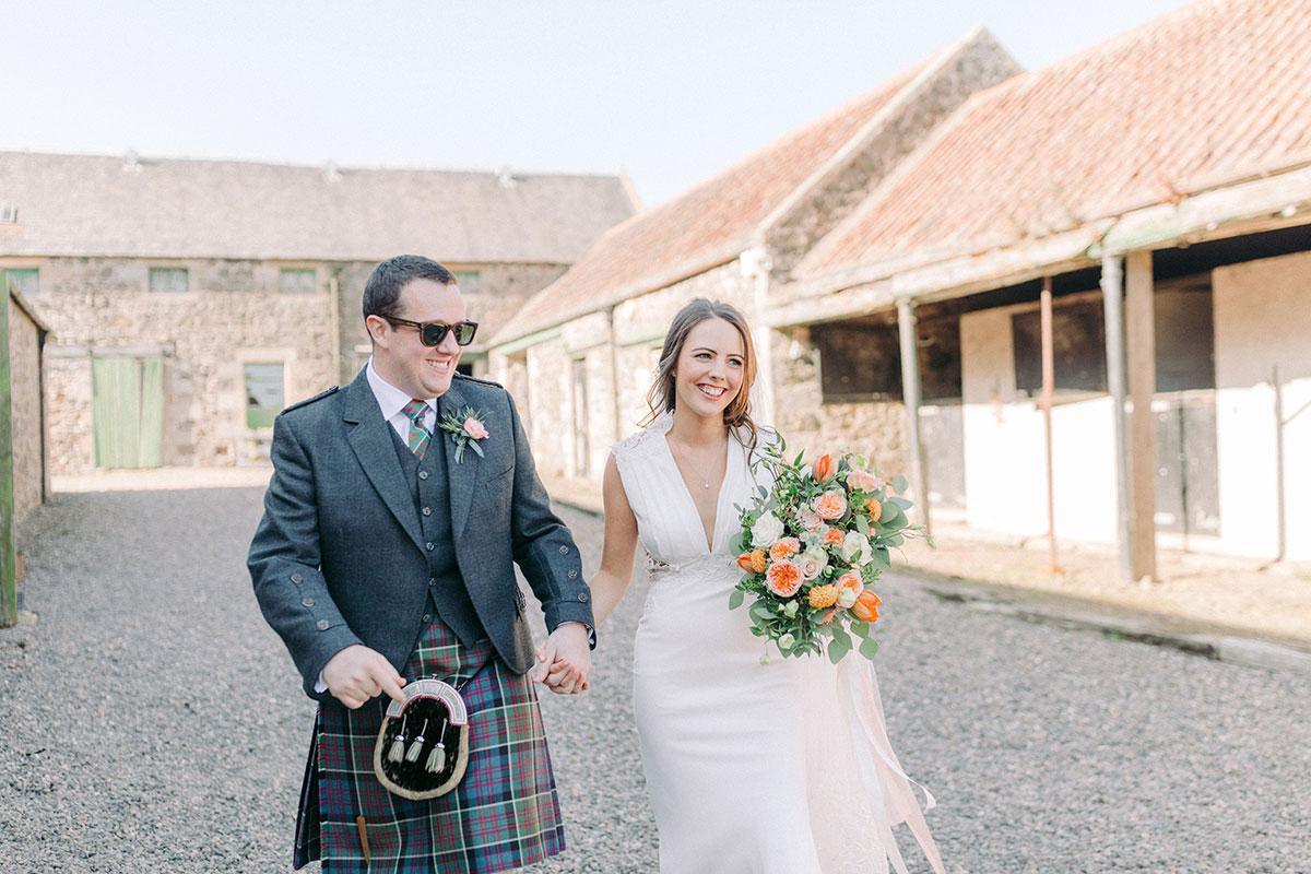 bride and groom walking in grounds at Pratis Barns
