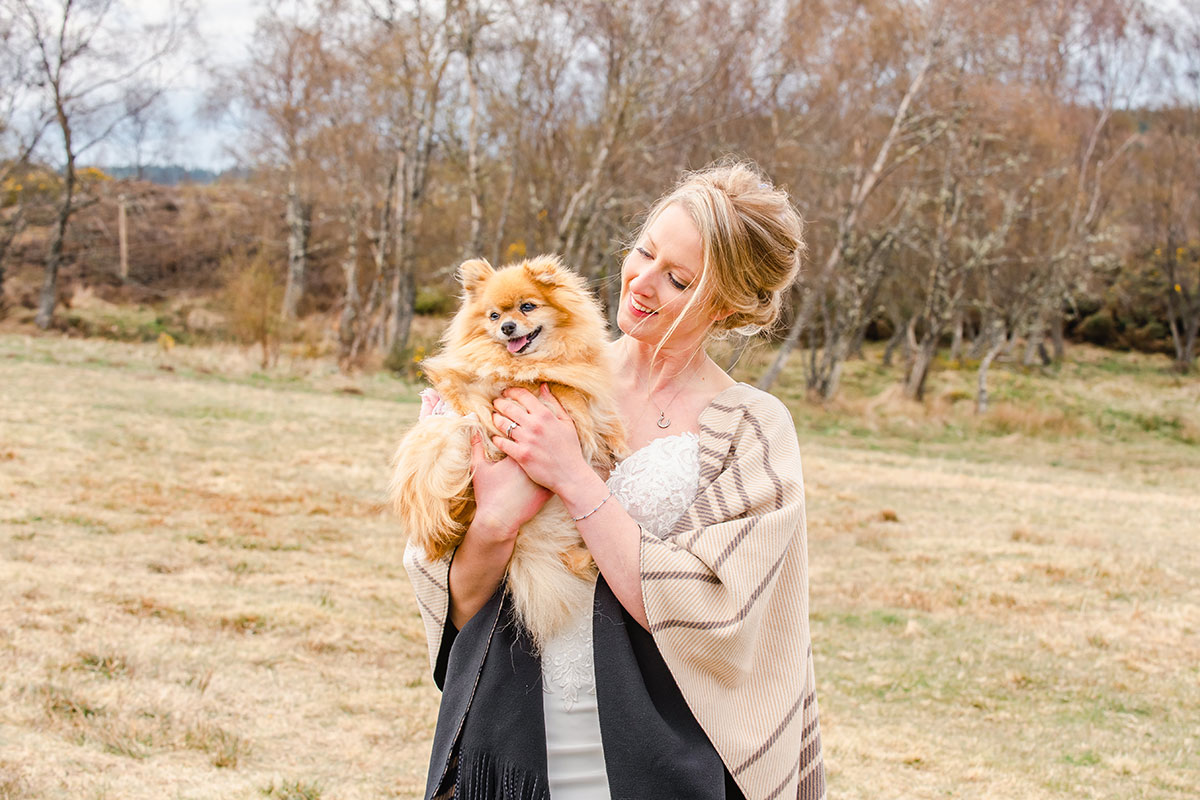 bride in countryside wearing shawl and looking smiling at pomeranian dog