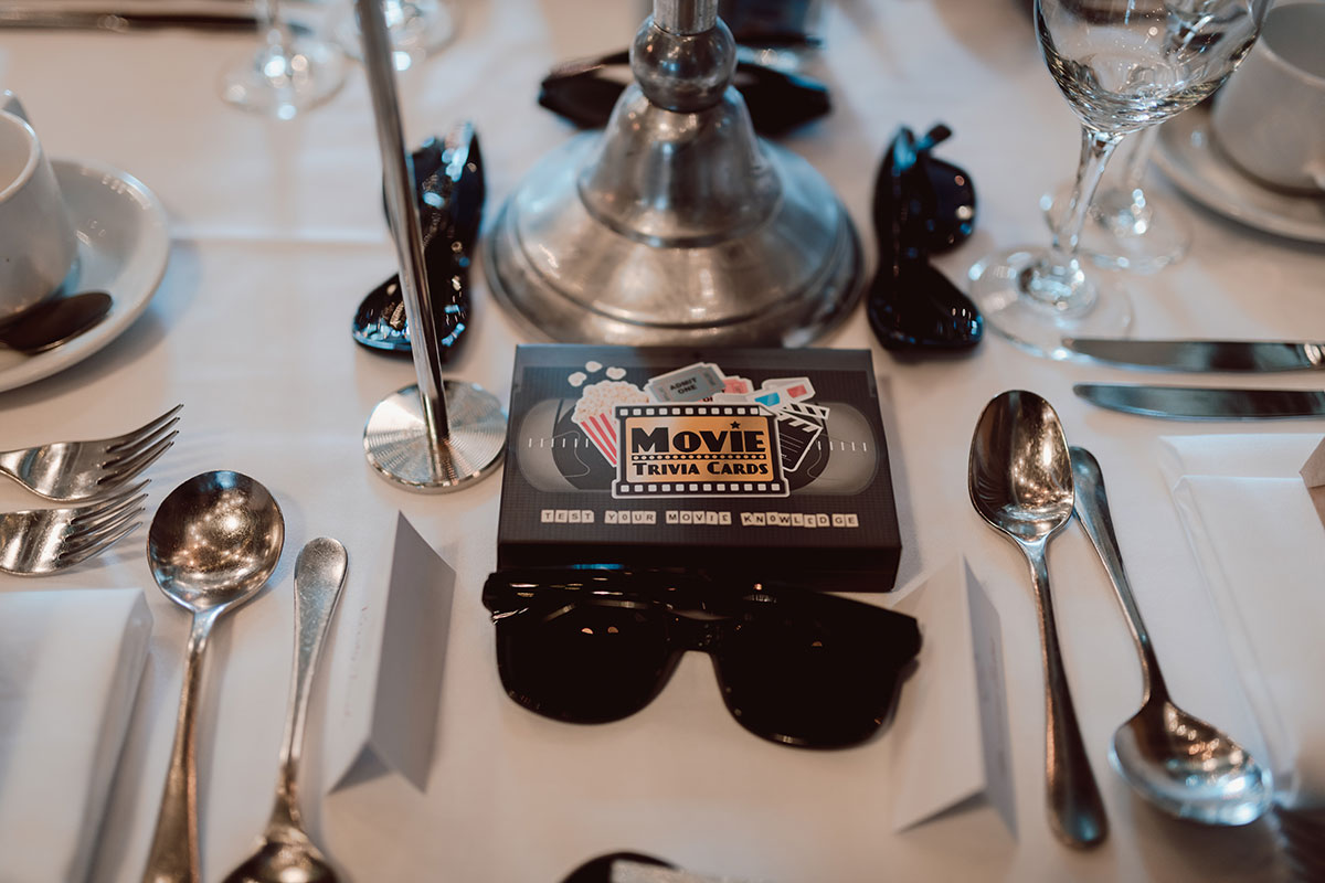 movie trivia cards and sunglasses on a table set for dinner