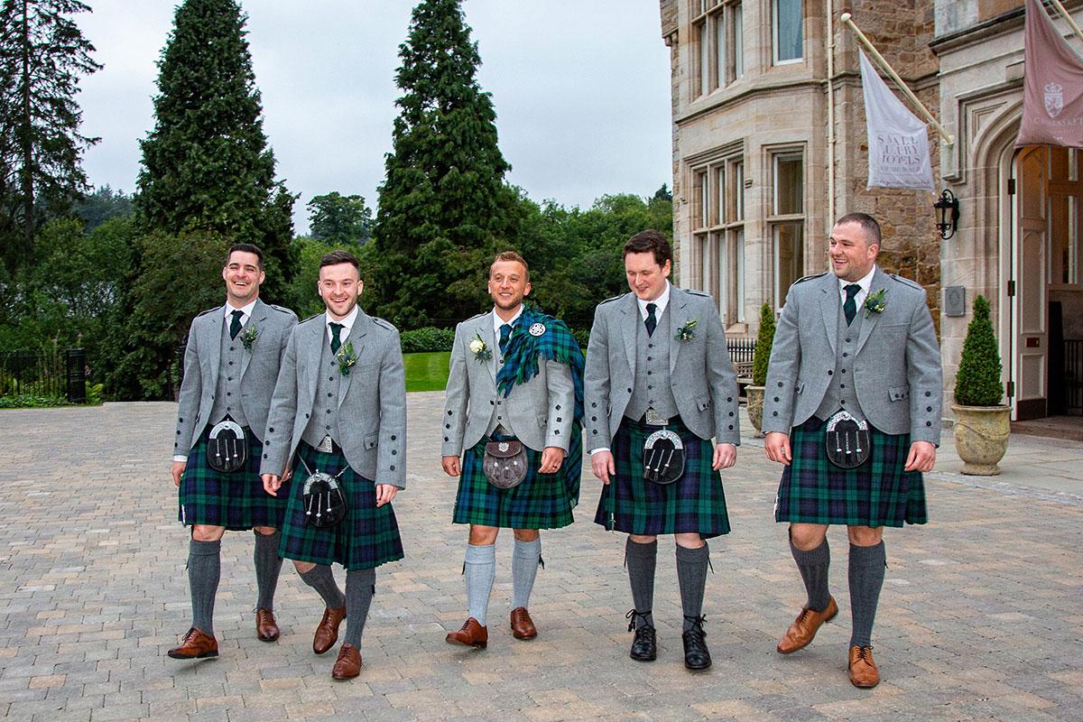 5 men in kilts walking in the grounds of Crossbasket Castle