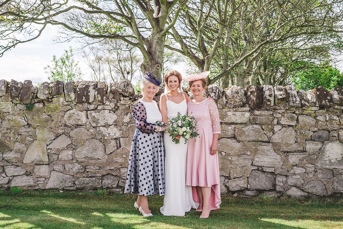 a bride with her mum and grandmother on her wedding day