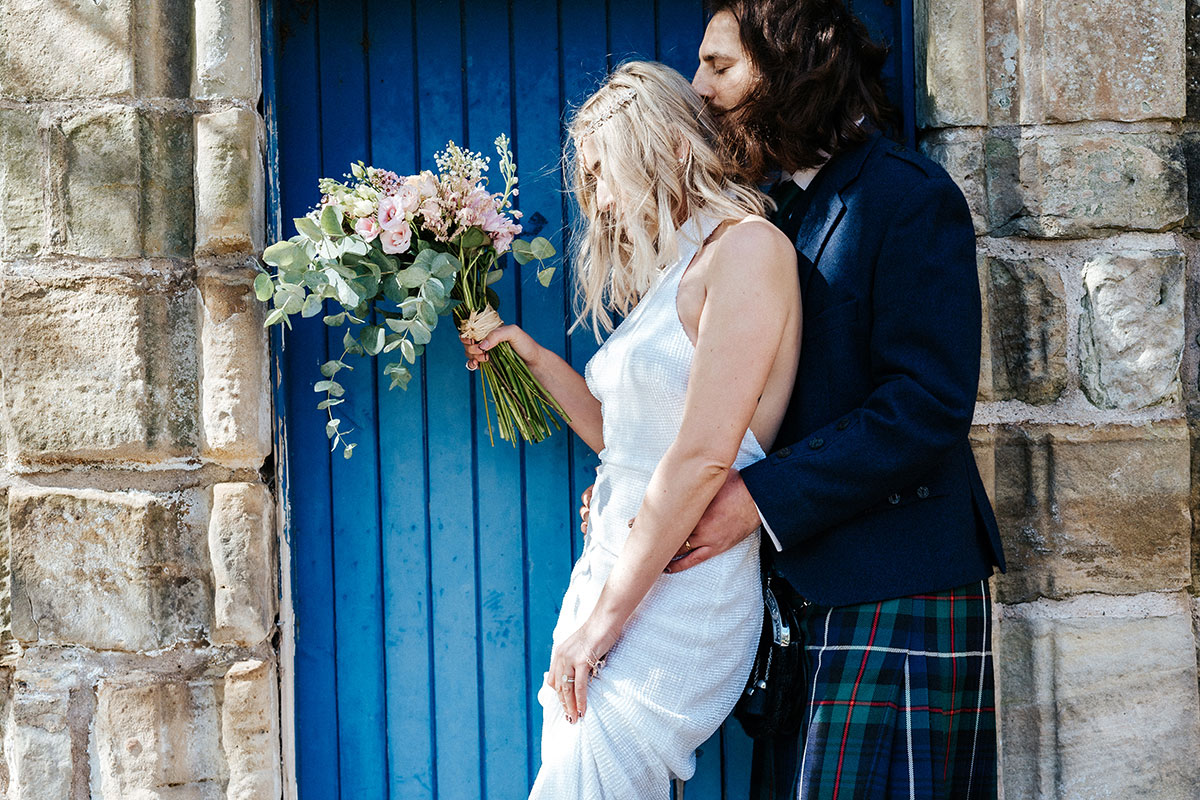 a groom kissing the back of a bride's head while they are standing in front of a blue door