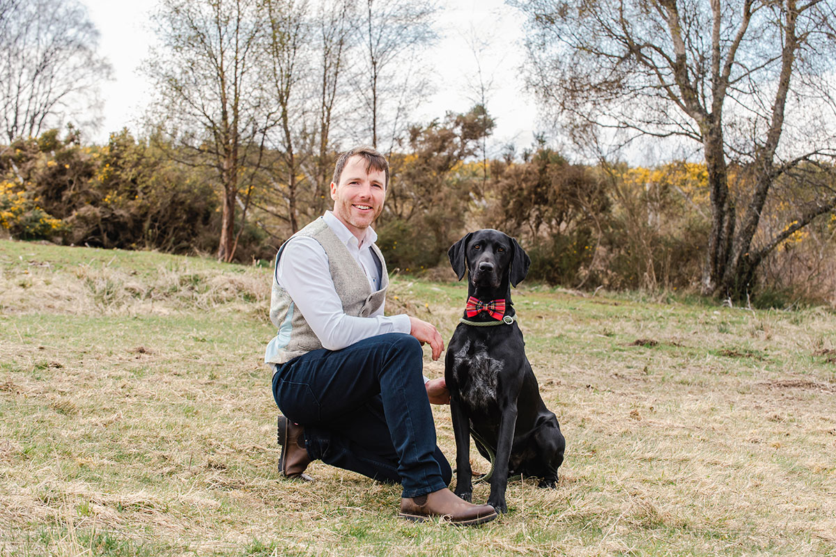 groom in the countryside posing alongside black Labrador wearing red bow tie