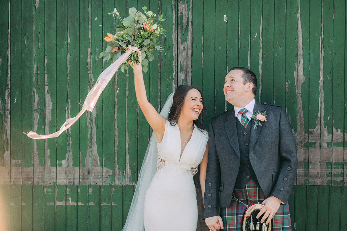 groom with bride raising bouquet in air against a green painted wooden door