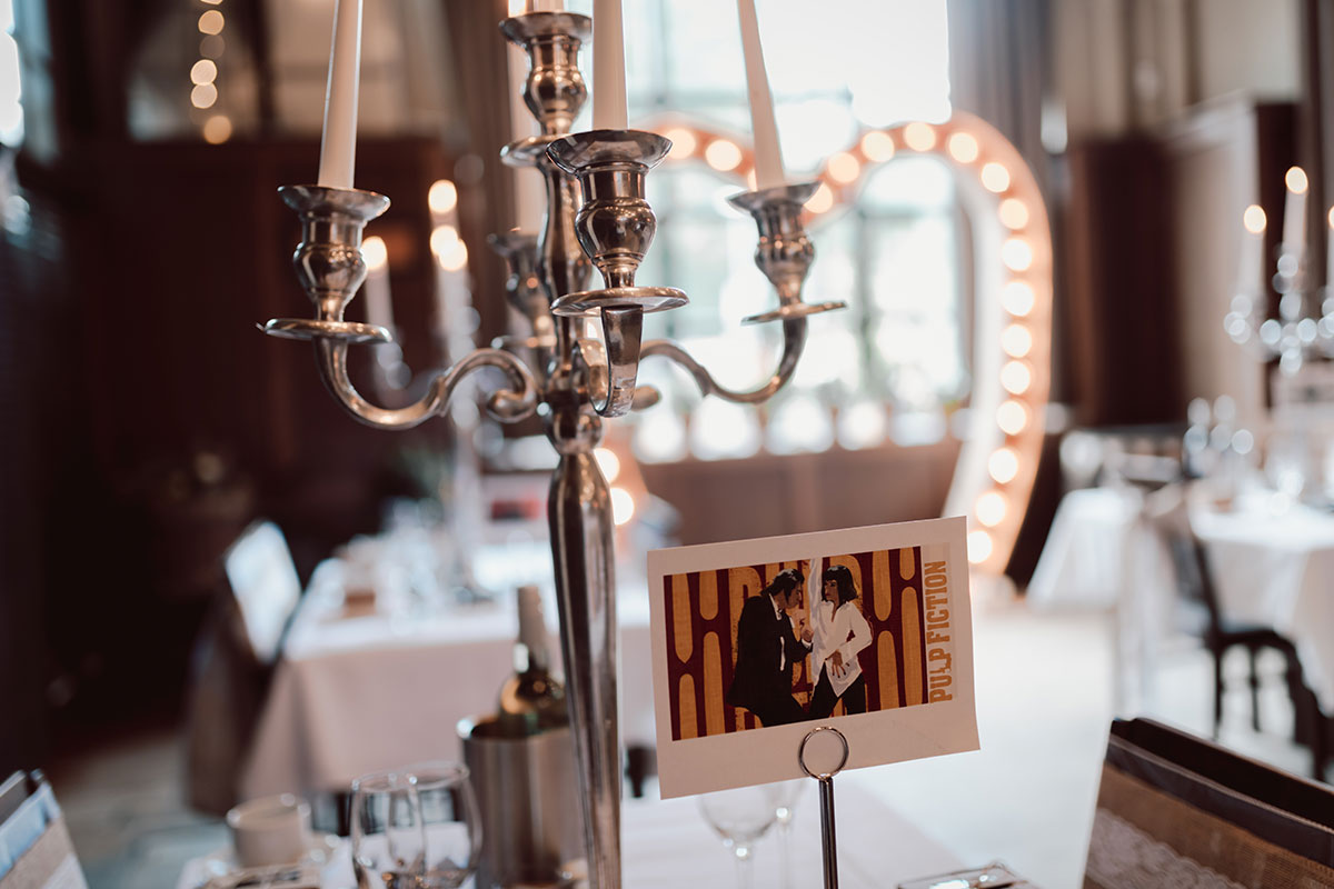 silver candelabra and Pulp Fiction wedding table name sign with illuminated heart arch decoration in background