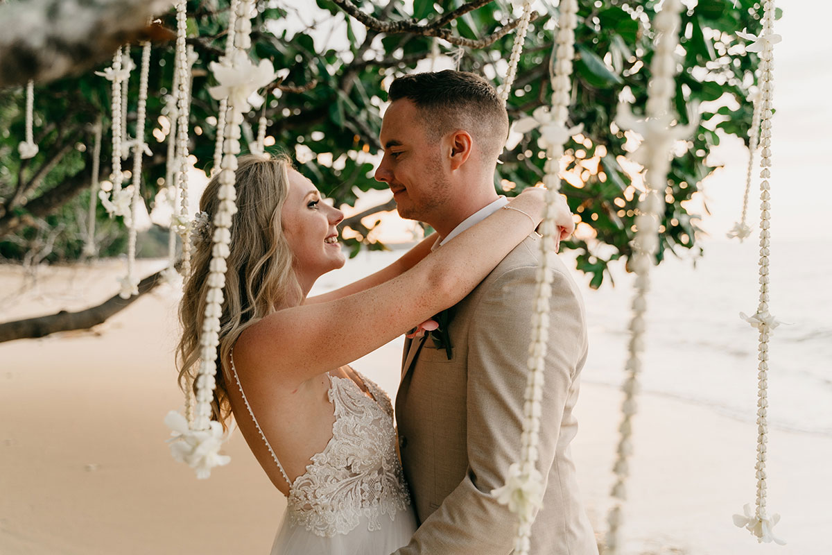 bride and groom kissing on the beach in thailand