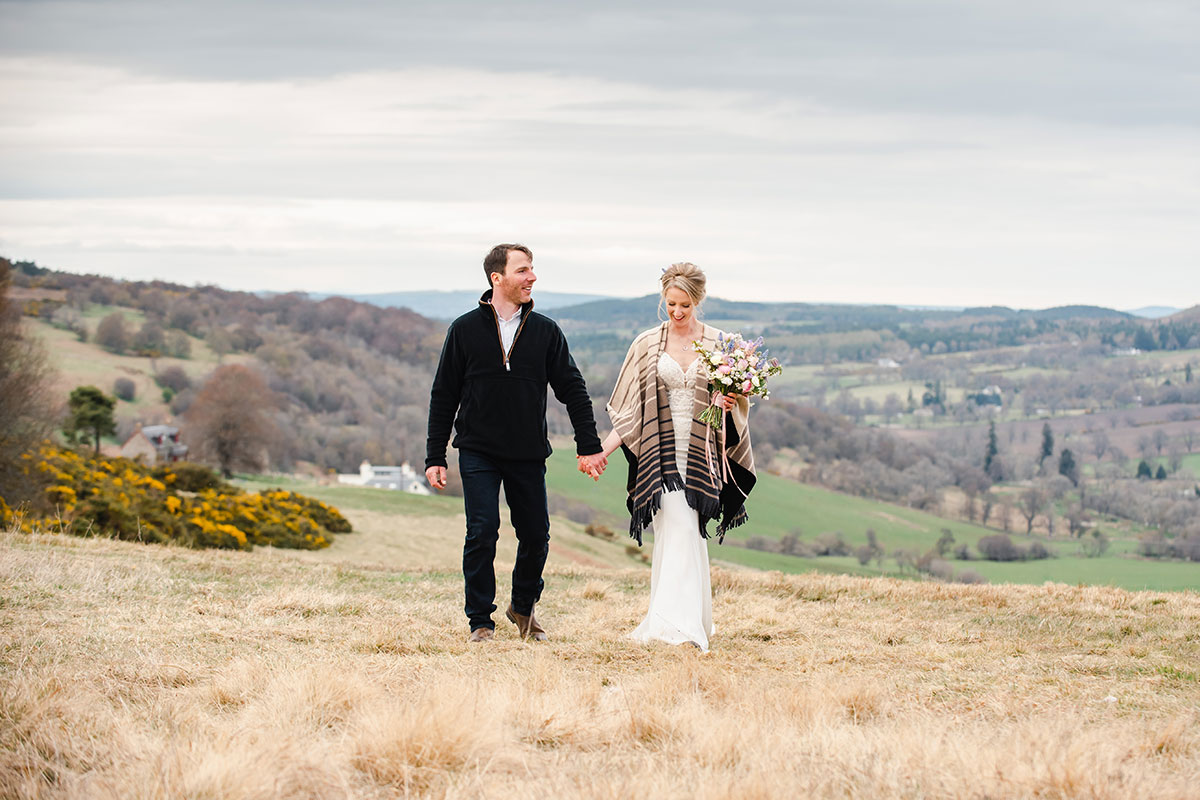 bride and groom strolling hand and hand in field in Scottish countryside