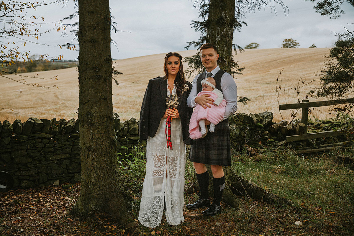 bride and groom with baby next to a field and trees
