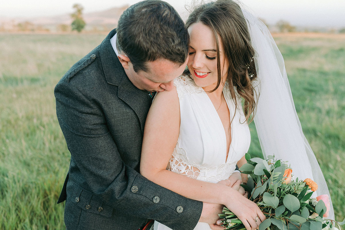 groom kissing bride on shoulder in green countryside setting