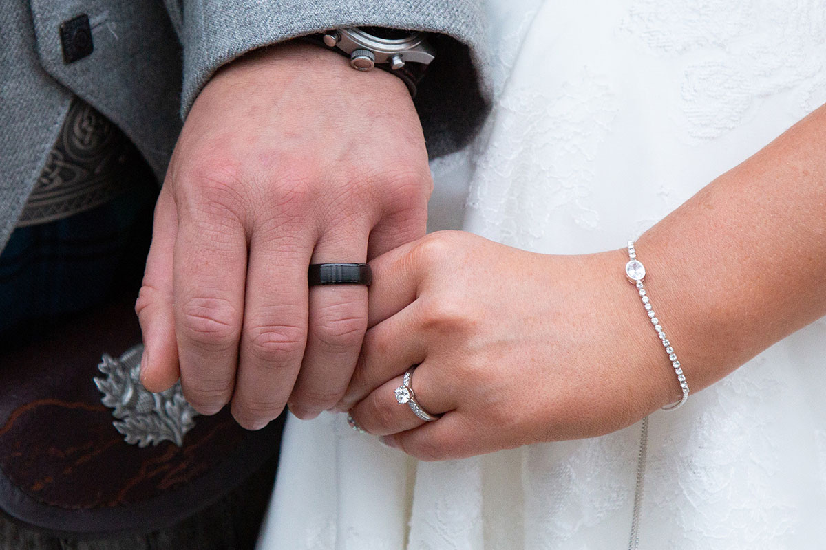 hands of a bride wearing diamond bracelet and ring and groom wearing black wedding ring