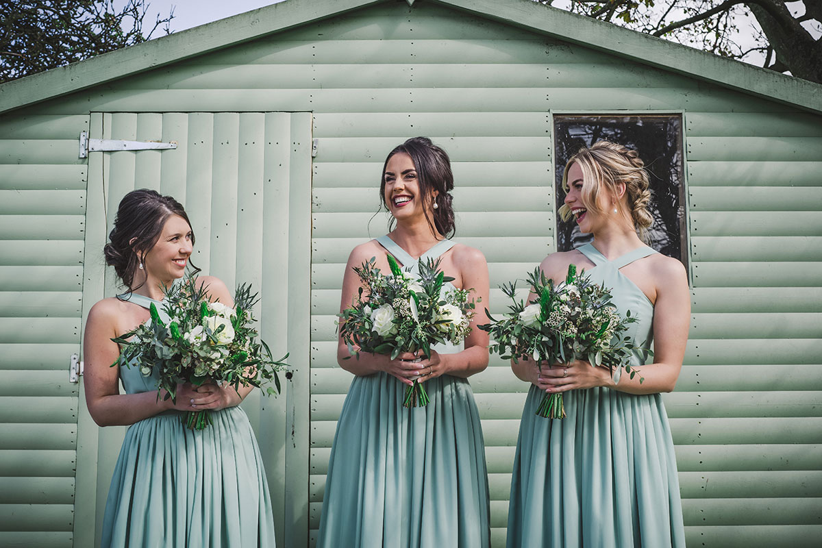 three bridesmaids wearing green laughing against a green shed